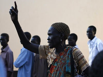 A women gestures after she votes in front of a polling station located in a school during a referendum in the town of Abyei