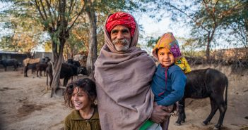 The healthcare crisis in India is significant but organizations like Momentum Global seek to fix it. The image shows a man with his grandchildren in Jaipur, Rajasthan in India.